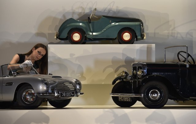 "Curator of Royal Collection Trust Anna Reynolds poses with a miniature Aston Martin DB5 presented to Prince Andrew in 1966 at Buckingham Palace – the official residence of Britain's Queen Elizabeth – in central London July 24, 2014. The exhibition ""Royal Childhood"" features well-loved toys, family gifts, and small outfits from over 250 years of the British royal family. Displayed in the Palace Ballroom and Ball Supper Room, the exhibition forms part of the summer opening of Buckingham Palace where 19 state rooms are opened to the public. (Photo by Toby Melville/Reuters)"