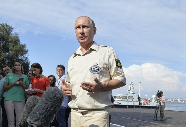 Russian President Vladimir Putin meets with journalists after submerging into the waters of the Black Sea inside a research bathyscaphe as part of an expedition in Sevastopol, Crimea, August 18, 2015. Putin on Tuesday blamed the Ukrainian government for the latest upsurge in fighting between Kiev forces and Russia-backed rebels in east Ukraine. (Photo by Alexei Druzhinin/Reuters/RIA Novosti/Kremlin)