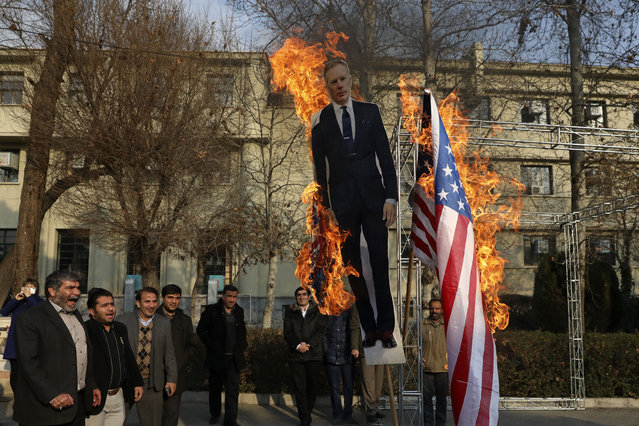 Pro-government protesters set fire to U.S. and British flags with a life size cut-out of Britain's ambassador to Tehran Rob Macaire, in a gathering to commemorate the late Iranian Gen. Qassem Soleimani, who was killed in Iraq in a U.S. drone attack on January 3, and victims of last week's Ukrainian plane crash outside Tehran, at the Tehran University campus in Tehran, Iran, Tuesday, Jan. 14, 2020. (Photo by Vahid Salemi/AP Photo)
