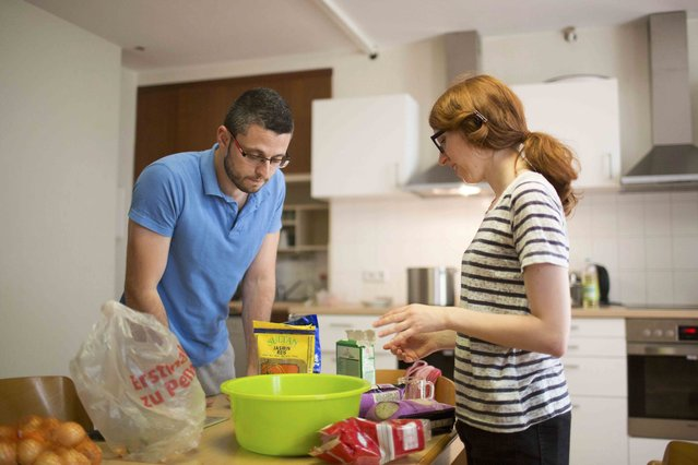 """Syrian migrant Eyad Ibrahim Aghe prepares a meal together with Denise Lillge, the accountant of the  """"Sharehaus Refugio"""" community in Berlin, where Germans and migrants live together, Germany August 19, 2015. (Photo by Axel Schmidt/Reuters)"""