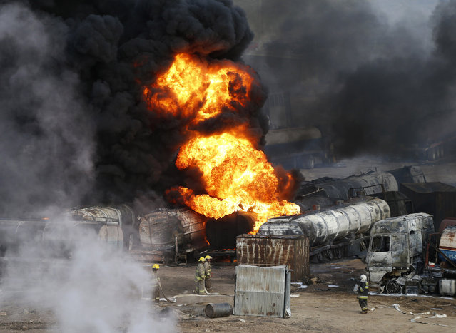 Smoke and flames rise from fuel trucks after an overnight attack by the Taliban on the outskirts of Kabul July 5, 2014. Taliban insurgents set fire on Saturday to about 200 oil tanker trucks supplying fuel for NATO forces in an attack just outside the Afghan capital Kabul, police said. (Photo by Mohammad Ismail/Reuters)