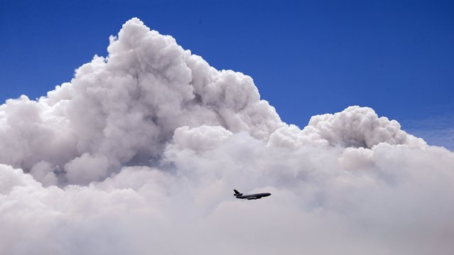 A DC-10 air tanker is dwarfed by the tip of a rising smoke cloud as the plane prepares to drop fire retardant over a wildfire near Carlton, Washington, on July 19, 2014. A wind-driven, lightning-caused wildfire racing through rural north-central Washington destroyed about 100 homes Thursday and Friday, leaving behind solitary brick chimneys and burned-out automobiles as it blackened hundreds of square miles in the scenic Methow Valley northeast of Seattle. (Photo by Elaine Thompson/AP Photo)