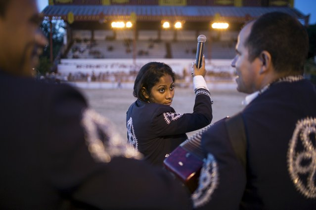 Mariachi Diana Sanchez, 23, talks to members of her band during a presentation at the International Livestock Fair Show in Havana, March 16, 2015. (Photo by Alexandre Meneghini/Reuters)