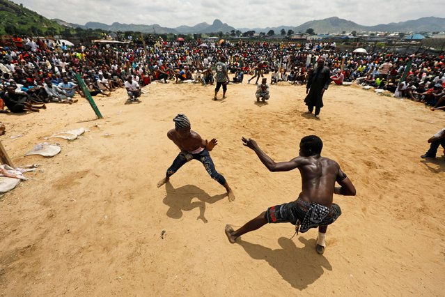 Dambe warriors fight in the ring, the ancient brutal martial art of Dambe associated with Hausa people of West Africa during a weekend match in Dei-Dei, Abuja, Nigeria on June 30, 2019. Matches last three rounds, which have no time limits. A round ends when there is no activity, a participant or official halts the round, or a fighter's hand, knee or body touches the ground. (Photo by Afolabi Sotunde/Reuters)