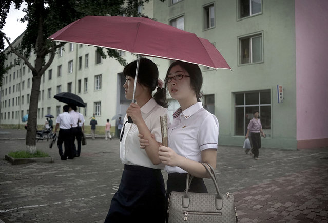 In this July 29, 2015 file photo, girls share an umbrella as they walk down a street in Pyongyang, North Korea. The rainy season in North Korea usually lasts through the month of July. (Photo by Wong Maye-E/AP Photo)