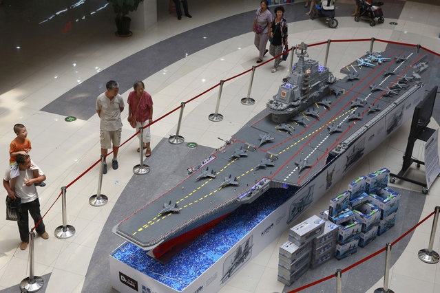 """People look at a replica of Chinese aircraft carrier """"Liaoning"""" made of toy building blocks, on display at a shopping mall in Shenyang, Liaoning province August 10, 2014. The replica, which measures 9-metres-long, 1.78-metres-wide and 1.6-metres-high, was made using a total of 443,800 pieces of toy blocks and took six people 180 days to finish, local media reported. (Photo by Reuters/Stringer)"""