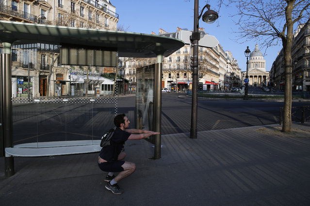 A man practices exercise next to the Pantheon, in Paris, Sunday, March 22, 2020. French President Emmanuel Macron urged employees to keep working in supermarkets, production sites and other businesses that need to keep running amid stringent restrictions of movement due to the rapid spreading of the new coronavirus in the country. (Photo by Francois Mori/AP Photo)
