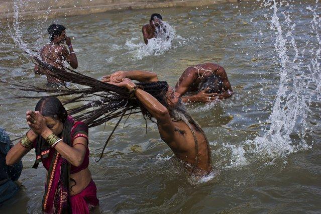 Hindu devotes take a bath in the Godavari River during Kumbh Mela, or Pitcher Festival, in Nasik, India, Saturday, August 29, 2015. (Photo by Bernat Armangue/AP Photo)