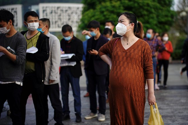 People wearing face masks line up outside Xianning Central Hospital in Xianning, after the lockdown was eased in Hubei province, the epicentre of China's coronavirus disease (COVID-19) outbreak, March 26, 2020. (Photo by Aly Song/Reuters)