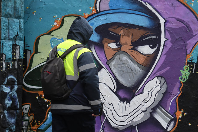 """A cyclist pushes his bicycle in front of a spray-painting graffiti showing a character with a face mask near the place where the """"Sziget"""" Island Festival in the Hajogyar (Shipyard) Island usually takes place on March 25, 2020 in Budapest. (Photo by Attila Kisbenedek/AFP)"""