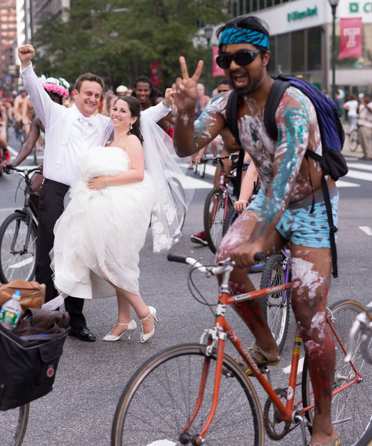 In this Saturday, August 29, 2015 photo, Ross Cohen, left, and Blair Delson celebrate their wedding day at the edge of Dilworth Plaza in Philadelphia, as participants in the annual Philly Naked Bike Ride pass by. (Photo by Joseph Gidjunis/JPG Photography via AP Photo)