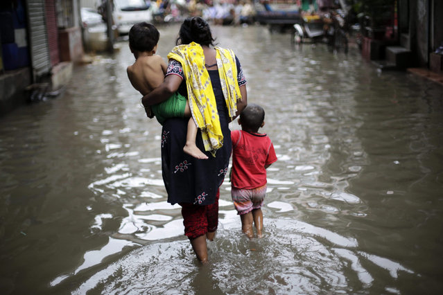 A woman and children walk through flood waters on the Nazim Uddin Road in Dhaka, Bangladesh 01 September 2015. According to local reports many streets have flooded after heavy downpours in the city causing residents to suffer with stagnant rain waters as the drainage and sewage system are overwhelming the poorly maintained infrastructure. (Photo by Abir Abdullah/EPA)