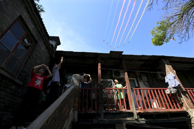 Local residents watch as military aircraft perform during the military parade marking the 70th anniversary of the end of World War Two, outside their house at a hutong in central Beijing, China, September 3, 2015. (Photo by Aly Song/Reuters)