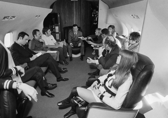 Playboy publisher Hugh Hefner, back center, sits on his DC-9 jetliner during a press conference after it landed, March 17, 1970, Los Angeles, Calif. Hefners companion, Barbi Benton is at right. The rest of the group is unidentified. (Photo by George Brich/AP Photo)