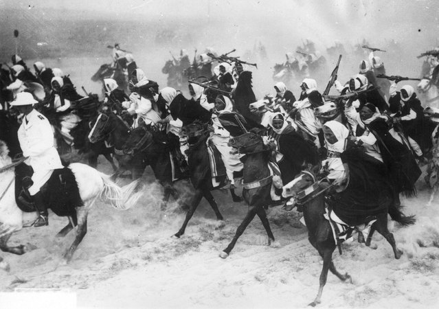 Libyan cavalrymen charging across the sand on horseback during a military display. 20th December 1939. (Photo by Keystone)