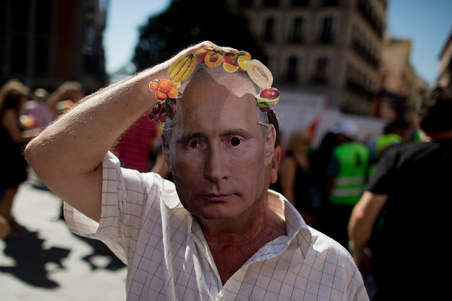 A man puts on a mask depicting Russian President Vladimir Putin wearing a fruit crown during a protest against the Russian food ban giving food away at Plaza Callao on September 5, 2014 in Madrid, Spain. Spanish farmers give away 10 tonnes of fruits to members of the public in Madrid in protest against Russia's ban on EU food imports and to promote the consumption of home grown produce. (Photo by Pablo Blazquez Dominguez/Getty Images)