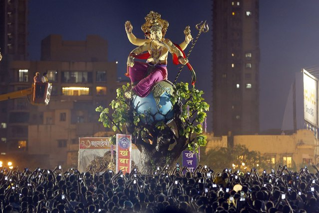 People take pictures as Indian Hindu devotees bring a large statue of the elephant-headed Hindu god Ganesha to immerse it in the Arabian Sea on the final day of the festival of Ganesh Chaturthi in Mumbai, India, Monday, September 8, 2014. Every year millions of devout Hindus immerse Ganesh idols into oceans and rivers during the ten-day long festival that celebrates the birth of Ganesha. (Photo by Rajanish Kakade/AP Photo)