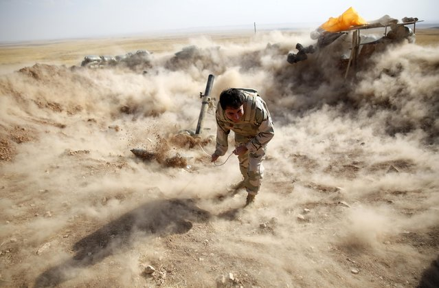 A Kurdish Peshmerga fighter launches mortar shells towards Zummar, controlled by Islamic State (IS), near Mosul September 15, 2014. (Photo by Ahmed Jadallah/Reuters)