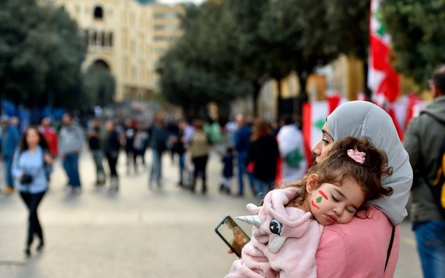 A woman carries her daughter during a protest in downtown Beirut, Lebanon, 01 December 2019. Protests in Lebanon are continuing since first erupted on 17 October, as protesters aim to apply pressure on the country's political leaders over what they view as a lack of progress following the prime minister's resignation on 29 October. (Photo by Wael Hamzeh/EPA/EFE)