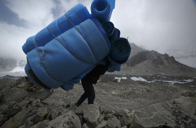 A porter carries mattresses back from Everest base camp, approximately 17388 feet above sea level, in Solukhumbu District May 6, 2014. (Photo by Navesh Chitrakar/Reuters)