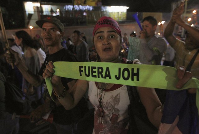 """A demonstrator gestures as she holds a headband reading """"Juan Orlando Hernandez out"""" during a march to demand the resignation of Honduras' President Hernandez in Tegucigalpa, September 11, 2015. The protesters are calling for the resignation of Hernandez over a $200-million corruption scandal at the Honduran Institute of Social Security. (Photo by Jorge Cabrera/Reuters)"""
