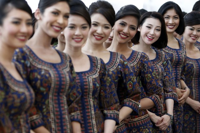 Singapore Airlines stewardesses, who will be appearing at the starting grid, stand together ahead of the Singapore F1 Grand Prix at the Marina Bay street circuit in Singapore September 21, 2014. (Photo by Edgar Su/Reuters)