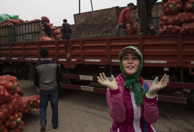 A Chinese vegetable vendor gestures as she wears rubber gloves while unloadeing a truck of onions at a local market on September 26, 2014 in Beijing, China. (Photo by Kevin Frayer/Getty Images)