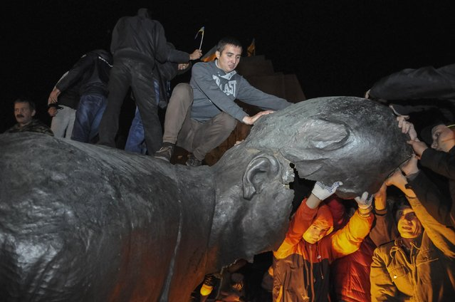 People react after a statue of Soviet state founder Vladimir Lenin was toppled by protesters during a rally organized by pro-Ukraine supporters in the centre of the eastern Ukrainian town of Kharkiv September 28, 2014. (Photo by Reuters/Stringer)