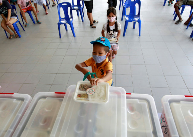 People from low-income communities receive free lunch boxes from volunteers during the coronavirus disease (COVID-19) outbreak in Bangkok, Thailand on May 13, 2020. (Photo by Soe Zeya Tun/Reuters)