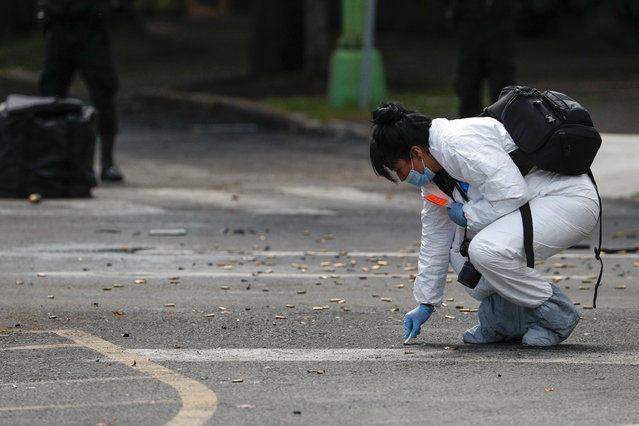 A forensic investigator collects cartridges at the scene where the Mexican capital's police chief was attacked by gunmen in Mexico City, Friday, June 26, 2020. Heavily armed gunmen attacked and wounded Omar García Harfuch in an operation that left several dead. (Photo by Rebecca Blackwell/AP Photo)