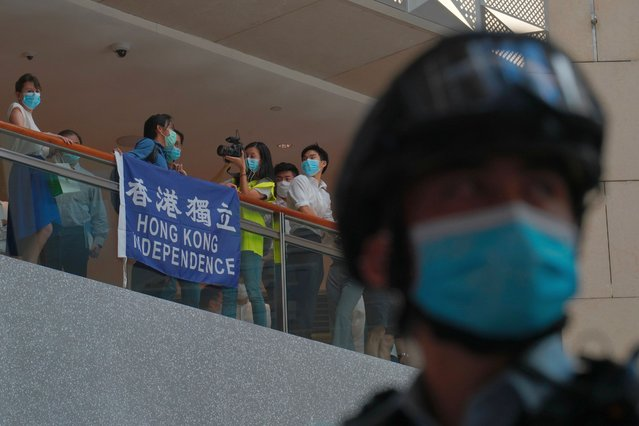A police officer stands guard as protesters gather at a shopping mall in Central during a pro-democracy protest against Beijing's national security law in Hong Kong, Tuesday, June 30, 2020. Hong Kong media are reporting that China has approved a contentious law that would allow authorities to crack down on subversive and secessionist activity in Hong Kong, sparking fears that it would be used to curb opposition voices in the semi-autonomous territory. (Photo by Vincent Yu/AP Photo)