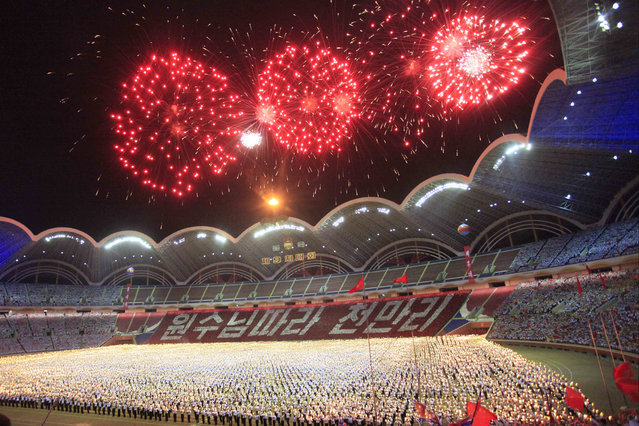 Participants carry torches on the field during a fireworks display as they parade during a celebration of the gathering of the country's main youth league at May Day Stadium in Pyongyang, North Korea, Sunday, August 28, 2016. The Kim Il Sung Socialist Youth League plays a major part in North Korea's social system, with young people aged 14 to 30 are expected to join and take part in activities ranging from study sessions to helping out in major construction projects. (Photo by Jon Chol Jin/AP Photo)