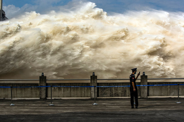 This photo taken on July 19, 2020 shows a security guard looking at his smartphone while water is released from the Three Gorges Dam, a gigantic hydropower project on the Yangtze river, to relieve flood pressure in Yichang, central China's Hubei province. Rising waters across central and eastern China have left over 140 people dead or missing, and floods have affected almost 24 million since the start of July, according to the ministry of emergency management. (Photo by AFP Photo/China Stringer Network)