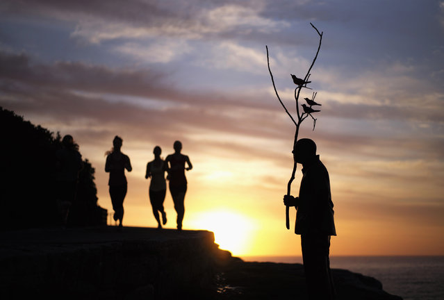 "A sculpture by Wang Shugang titled ""Men Playing with Birds"" is seen alongside joggers at sunrise at Tamarama Beach October 23, 2014. (Photo by Jason Reed/Reuters)"