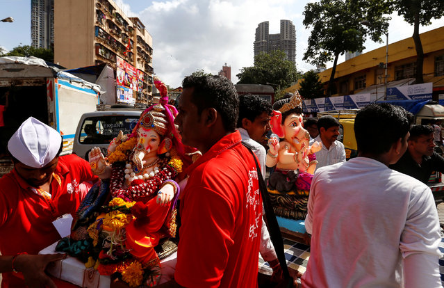 Idols of the Hindu god Ganesh, the deity of prosperity, are carried on handcarts to a place of worship on the first day of the Ganesh Chaturthi festival in Mumbai, India, September 5, 2016. (Photo by Danish Siddiqui/Reuters)