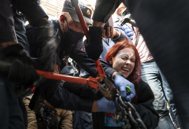 Police try to cut the handcuffs off a woman who handcuffed herself to a fence during a rally supporting Khabarovsk region's governor Sergei Furgal in St.Petersburg, Russia, Saturday, August 1, 2020. Thousands of demonstrators rallied Saturday in the Russian Far East city of Khabarovsk to protest the arrest of the regional governor, continuing a three-week wave of opposition that has challenged the Kremlin. (Photo by Dmitri Lovetsky/AP Photo)