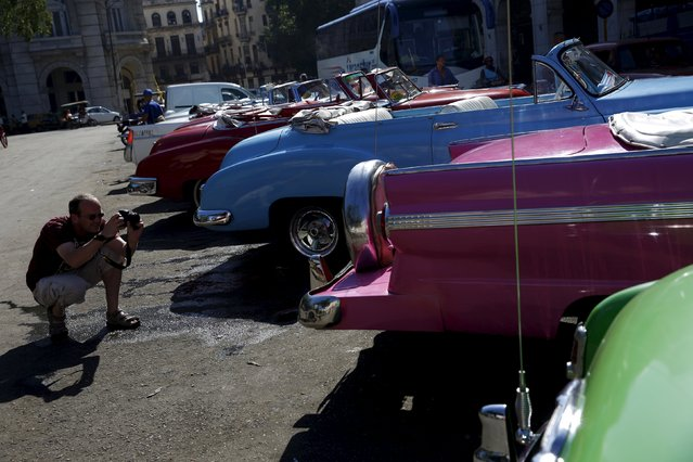 A tourist takes photographs of vintage cars in Havana September 18, 2015. (Photo by Carlos Garcia Rawlins/Reuters)