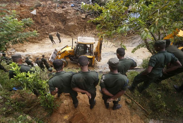 Members of a military rescue team watch as heavy equipment is used to clear debris at the site of a landslide at the Koslanda tea plantation near Haldummulla October 30, 2014. (Photo by Dinuka Liyanawatte/Reuters)