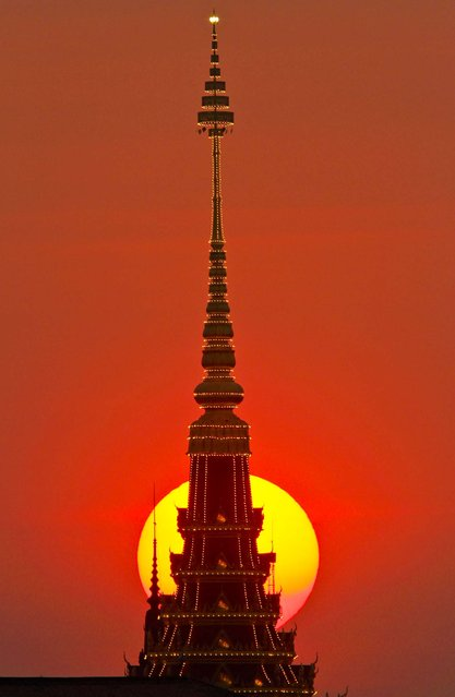 The sun sets behind a tower under construction for the cremation of Cambodia's late King Norodom Sihanouk, near the Royal Palace in Phnom Penh, January 18, 2013. The Royal Palace is scheduled to hold a rehearsal for Sihanouk's funeral on January 19. The former king died on October 15, 2012. He was 89. (Photo by Heng Sinith/Associated Press)