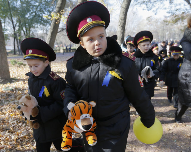 """Ukrainian cadets carry soft toys after they took part in meeting with slogan """"Thank you for life!"""" near of the monument for victims of the Nazi massacre in Babiy Yar, Kiev, Ukraine, October 28, 2014. Ukrainians mark 70th anniversary of the liberation of Ukraine from the Nazi occupation during WWII. (Photo by Sergey Dolzhenko/EPA)"""
