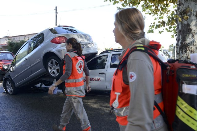 French Red Cross volunteers walk past an upended car on a street after flooding caused by torrential rain in Biot, France, October 4, 2015. (Photo by Jean-Pierre Amet/Reuters)
