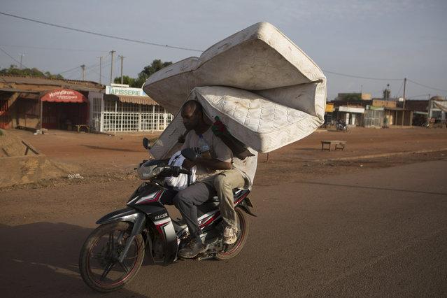 People transport a mattress in Ouagadougou, capital of Burkina Faso, October 30, 2014. (Photo by Joe Penney/Reuters)