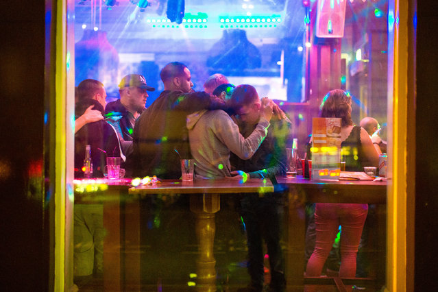 View through the window of men hugging close together, inside Yates Wine Lodge on Portland Street in Manchester, UK on September 11, 2016. (Photo by Joel Goodman/London News Pictures)