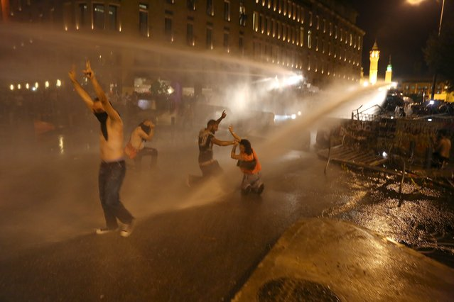 Protesters gesture with the victory sign while sprayed by water from police water cannons in Martyr square, downtown Beirut, Lebanon October 8, 2015. (Photo by Aziz Taher/Reuters)