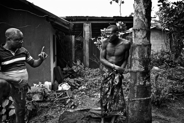"""""""Native Doctor Lekwe Deezia claims to heal mental illness through the power of prayer and traditional herbal medicines. While receiving treatment, which can sometimes take months, his patients are chained to trees in his courtyard. They are not given shelter or protection from the elements. One patient tells the photographer they are sometimes beaten for no reason. The Niger Delta, Nigeria, October 2012"""". (Photo and comment by Robin Hammond, New Zealand/2013 Sony World Photography Awards"""
