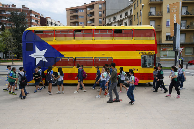 Young students walk past a bus decorated in the colours of the Catalan separatist flag, the Estelada, to collect signatures in favour of the right to hold a referendum in Vic, near Barcelona, April 11, 2014. (Photo by Albert Gea/Reuters)