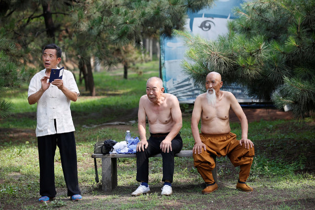 Kung Fu master Li Liangui (R) takes a break from his training Kung Fu with his friends at a park in Beijing, China, June 30, 2016. (Photo by Kim Kyung-Hoon/Reuters)