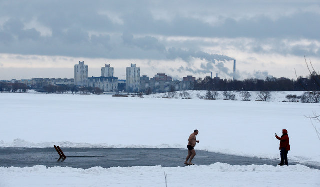 Man runs after diving in icy waters of a lake during Orthodox Epiphany celebrations in Minsk, Belarus January 19, 2018 on January 19, 2018. (Photo by Vasily Fedosenko/Reuters)