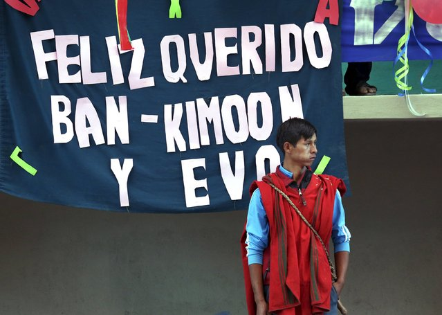 """A man stands next to a banner that reads """"Happy and dear Ban Ki-Moon and Evo"""" during the inauguration of a sports arena called """"Coliseo Ban Ki-Moon"""" in Vila Vila, south of Cochabamba, October 11, 2015. (Photo by David Mercado/Reuters)"""