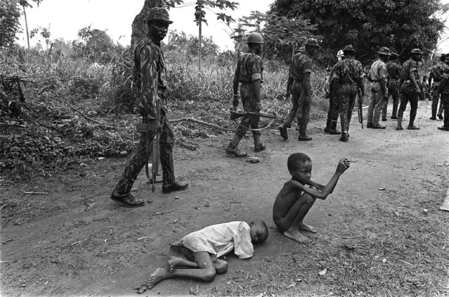 Federal Nigerian troops walk along a road near Ikot Expene, Nigeria, to the frontier with Biafra, a few miles away, October 13, 1968. On the roadside two emaciated Nigerian boys slowly die from starvation and malnutrition. (Photo by Dennis Lee Royle/AP Photo)